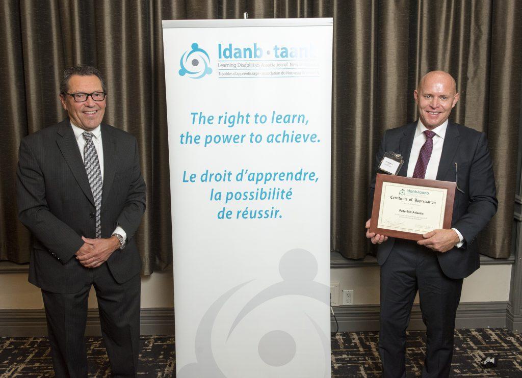 LDANB Board President, Roger Duval presents framed certificate to Tim Hawkins, CEO of Peterbilt Atlantic.